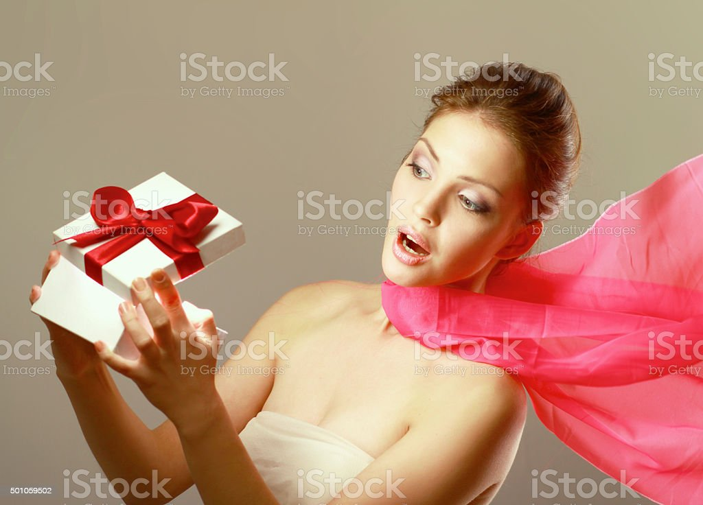 Girl opening x-mass present isolated on grey background stock photo
