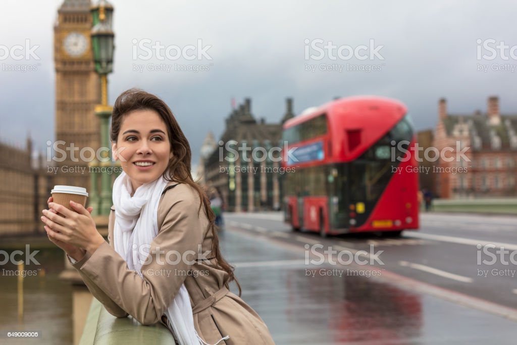 Girl or young woman drinking coffee in a disposable cup on Westminster Bridge with Big Ben and red double decker bus in the background, London, England, Great Britain stock photo