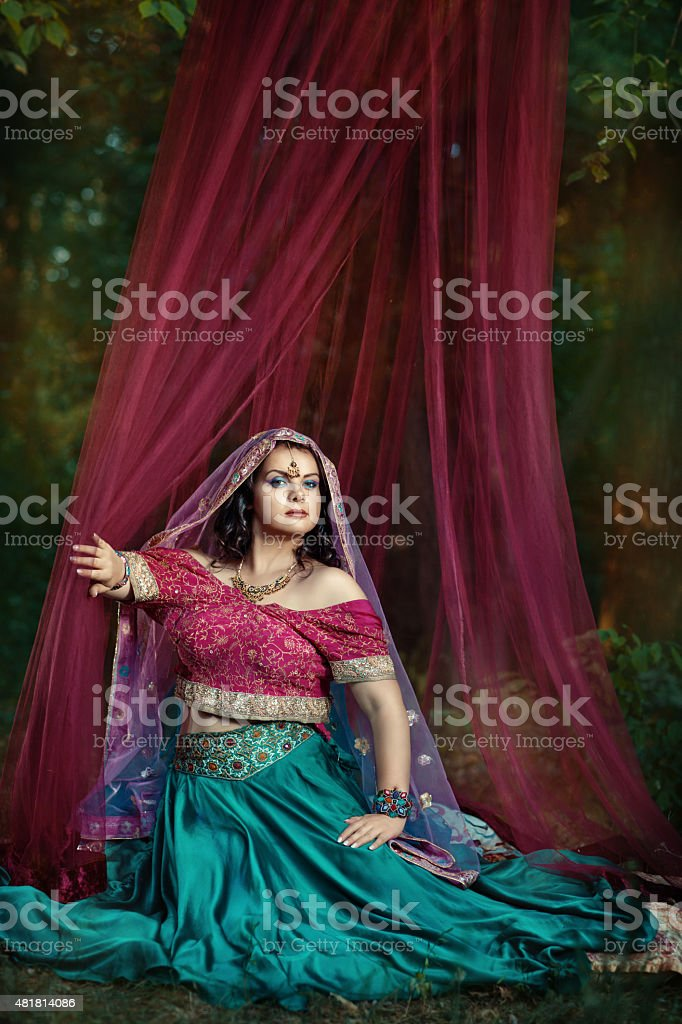 Girl oriental clothes sitting in a tent. stock photo