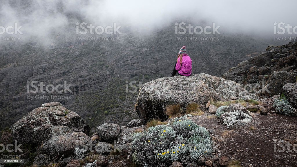 Girl over cliff in mountains, freedom concept stock photo