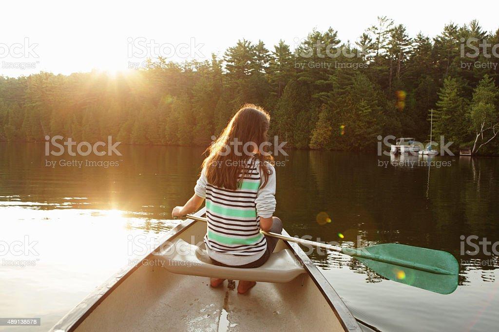 Girl paddling canoe on a lake as the sun rises stock photo