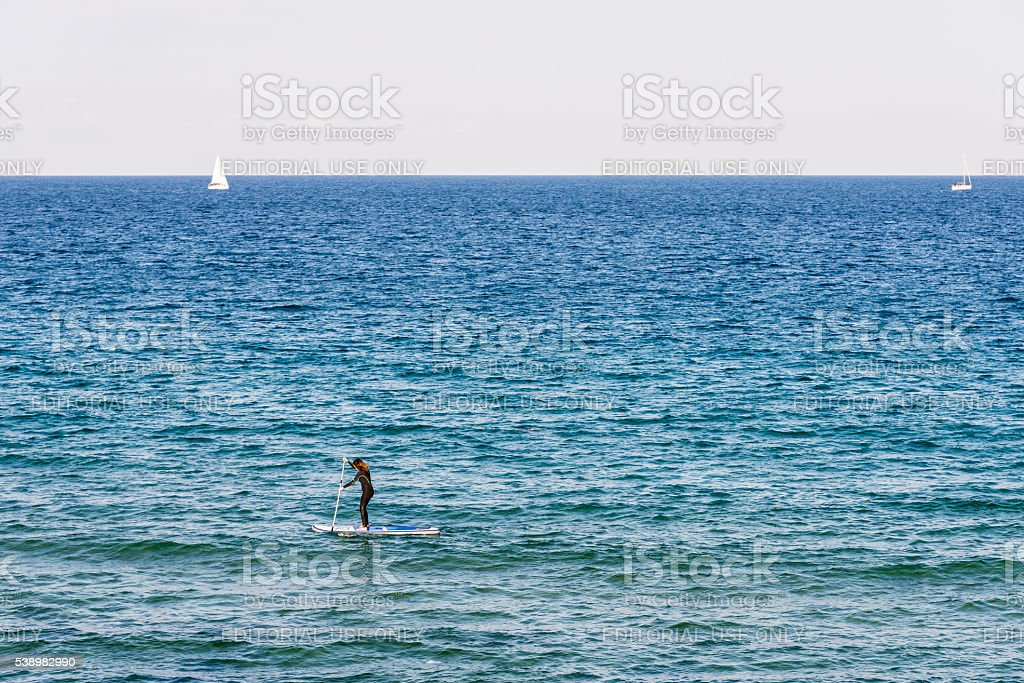 Girl paddling on a surfboard stock photo