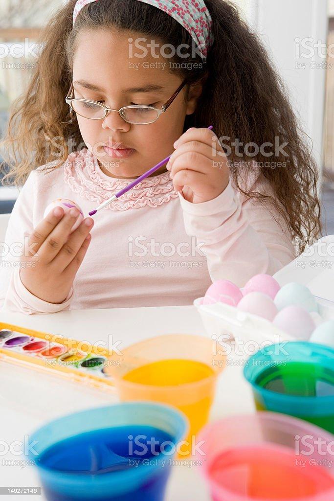 Girl painting an egg for easter stock photo