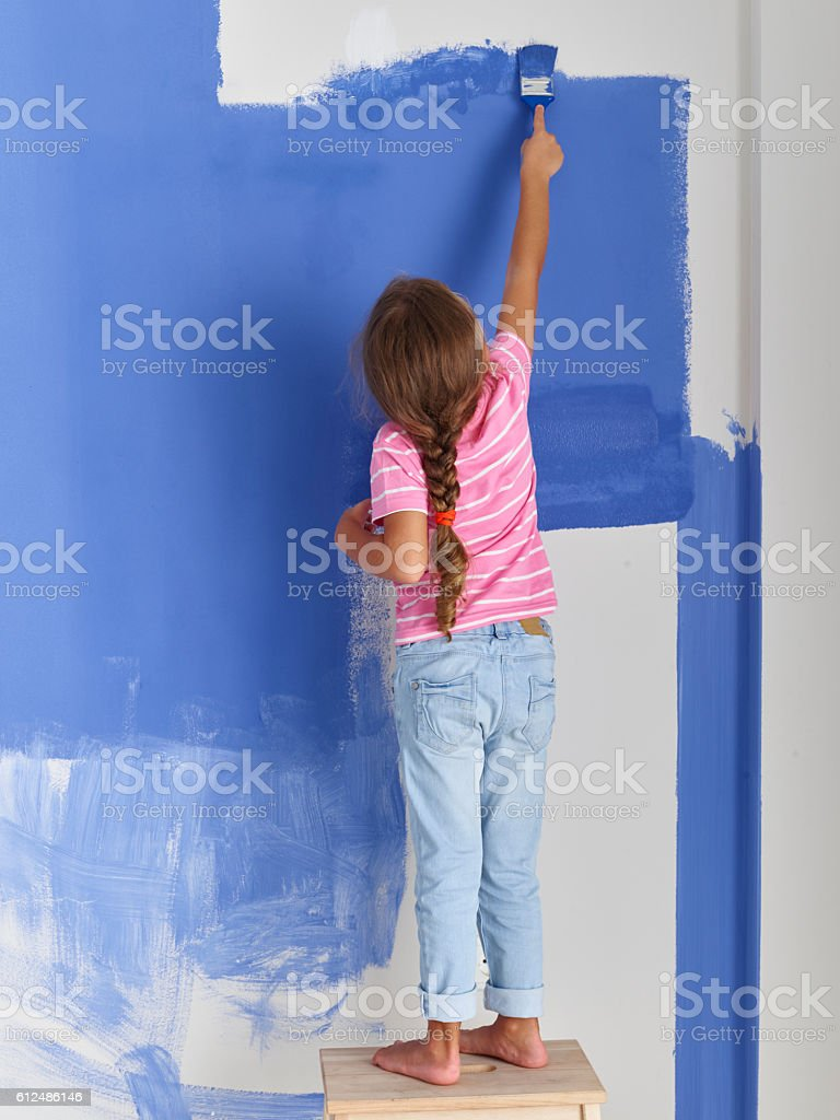 Girl painting wall with paintbrush stock photo