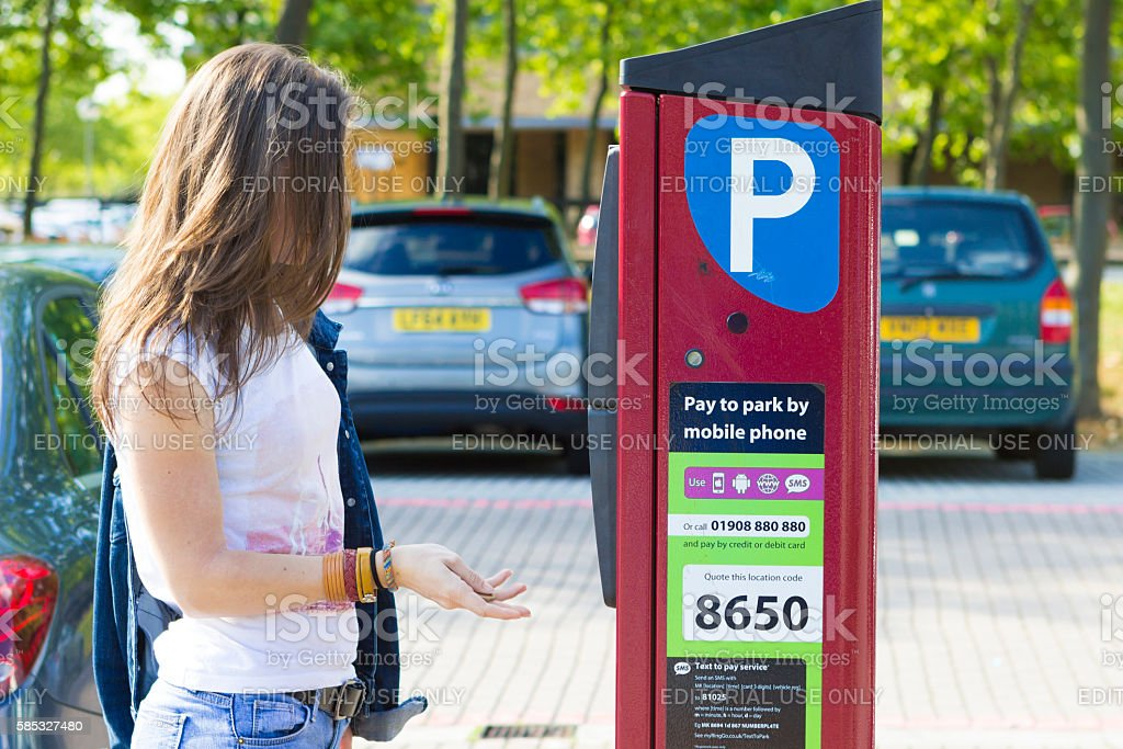 Girl paying for parking, Milton Keynes stock photo