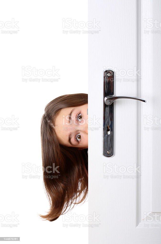 Girl peeking behind the door stock photo