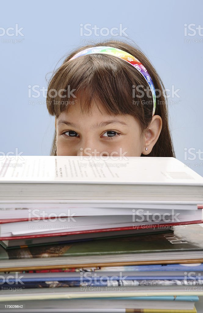 Girl peeking over stack of books isolated on blue royalty-free stock photo