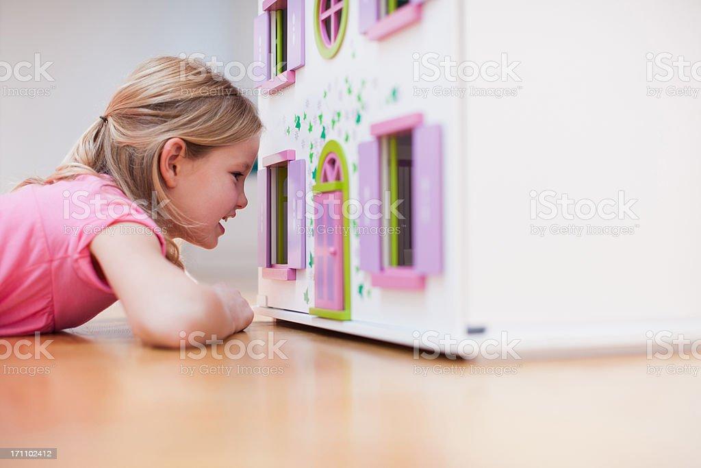 Girl peering into dollhouse stock photo