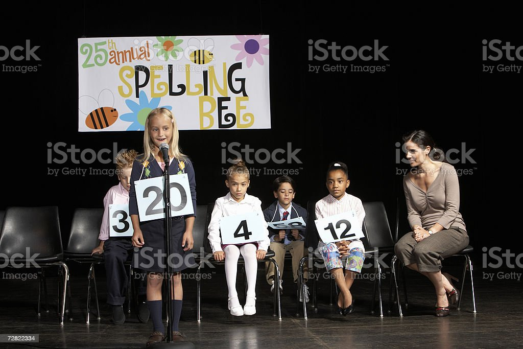 Girl (6-7) performing at spelling bee competition stock photo