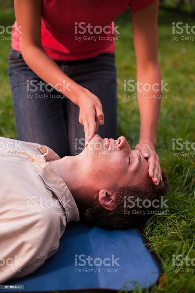 Girl performing first aid on a man stock photo