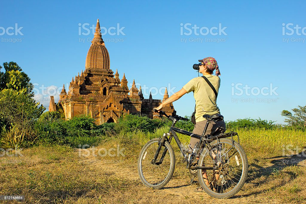 girl photographer on bicycle takes picture of the temple in stock photo
