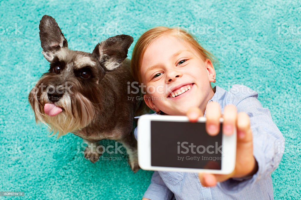 Girl photographing herself and her dog stock photo