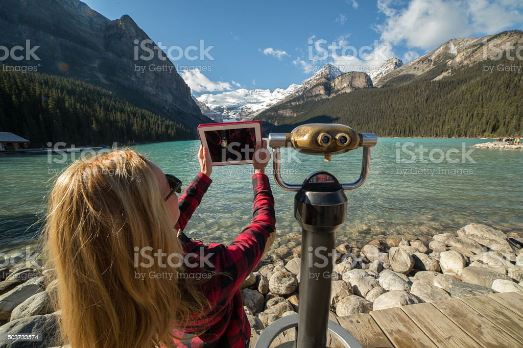 Girl photographing landscape using digital tablet-Lake Louise stock photo