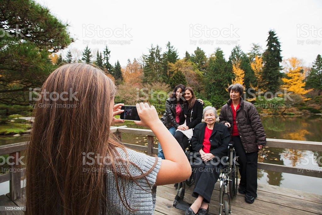 Girl photographing multi generation family stock photo