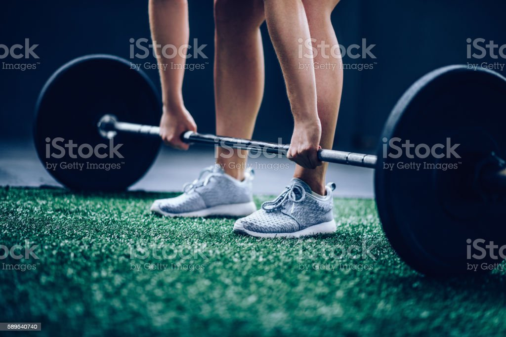 Girl picking up heavy barbell with weights for workout stock photo