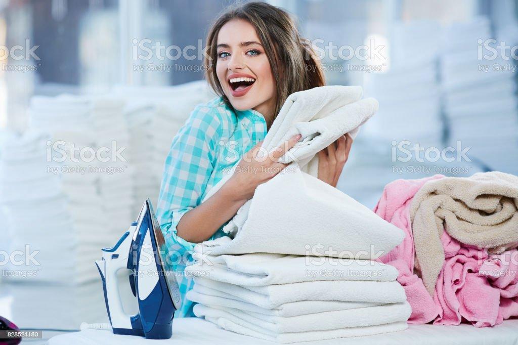 Girl piling white linen into heap stock photo