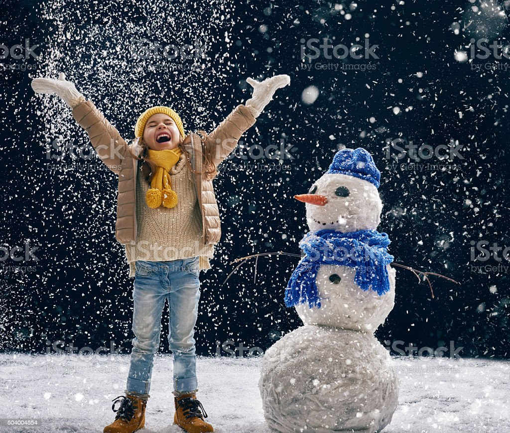 girl plaing with a snowman stock photo