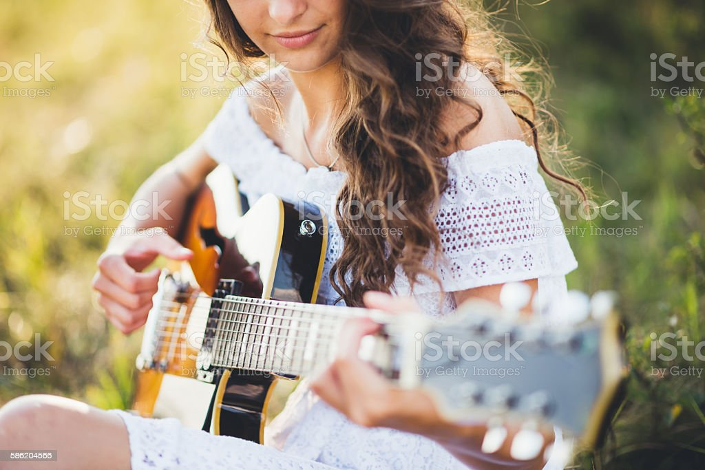 Girl playing a guitar in nature stock photo