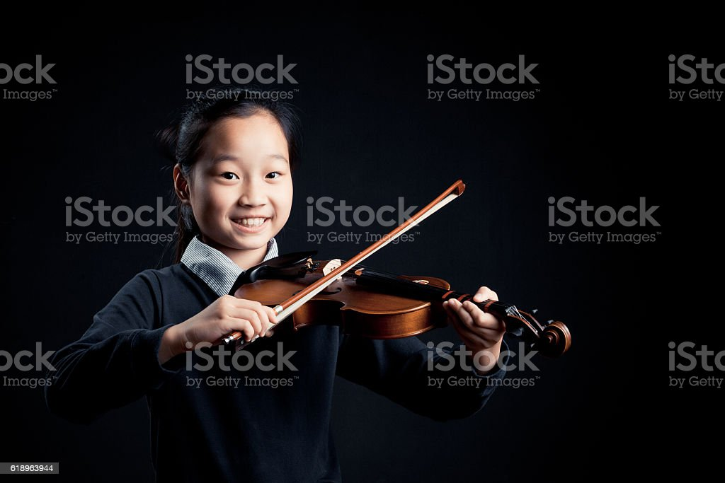 girl playing a Violin isolated over a black background stock photo