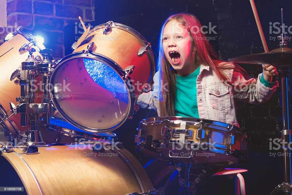 Girl playing drums stock photo