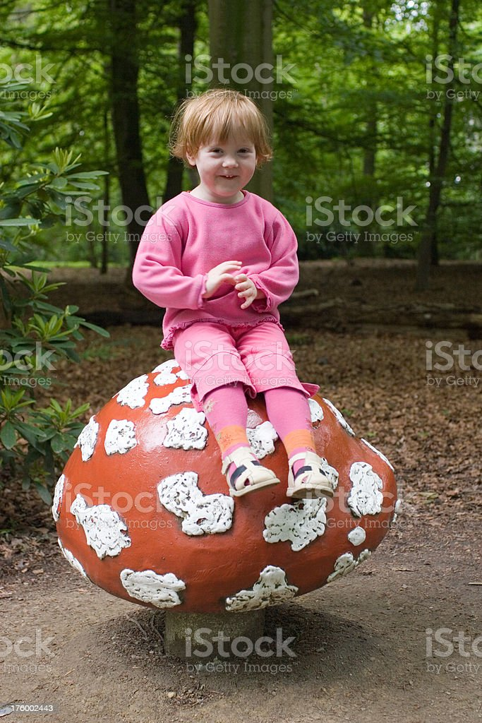 girl playing Dwarf on a toadstool in the forest royalty-free stock photo