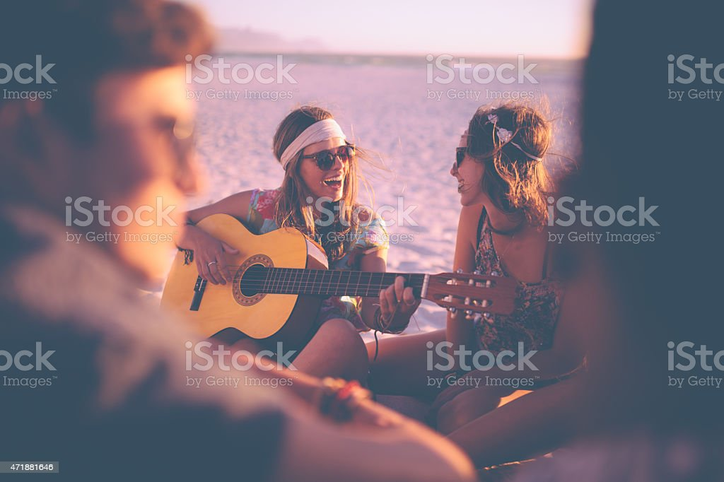 Girl playing guitar for her friends at a beachparty stock photo