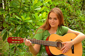Girl playing guitar in the nature