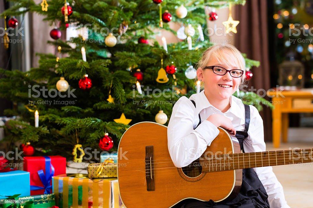 Girl playing guitar on Christmas day stock photo
