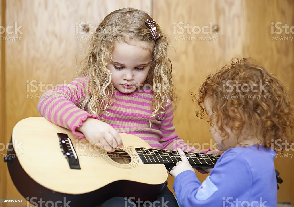 Girl Playing Guitar with Little Sister royalty-free stock photo