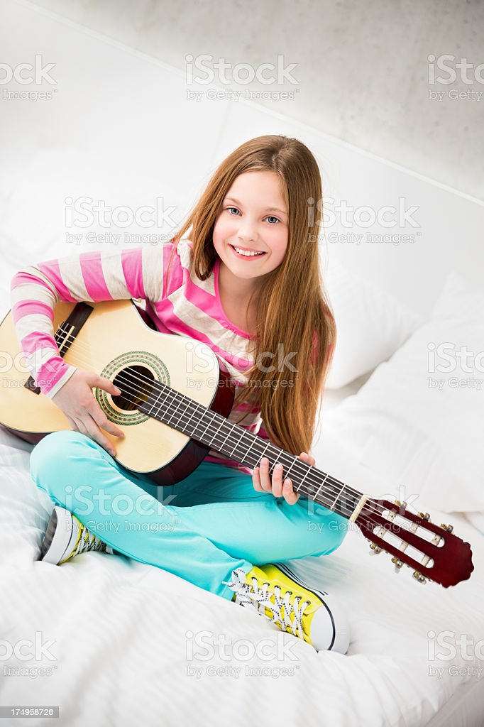 Girl playing her guitar royalty-free stock photo