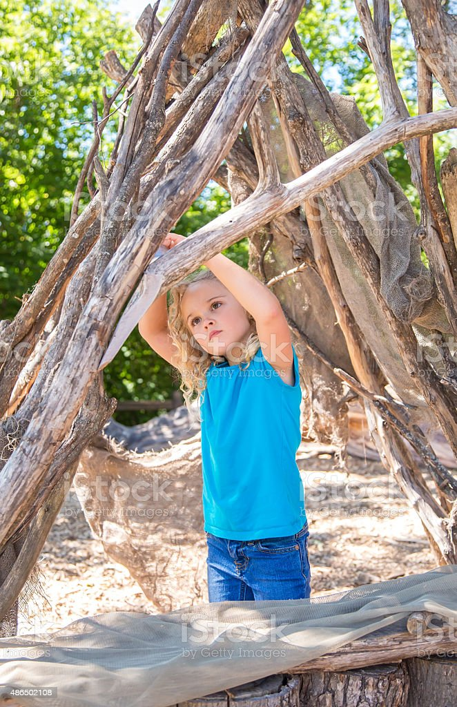 Girl Playing in Fort Made From Logs & Branches stock photo