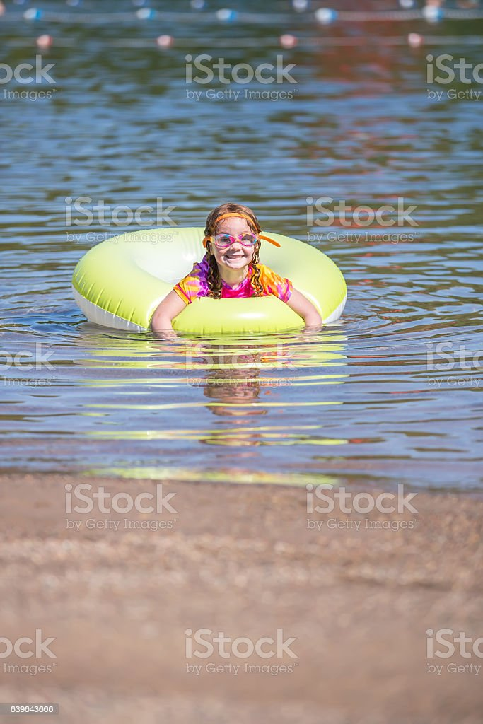Girl Playing In Inner Tube Float at Beach stock photo