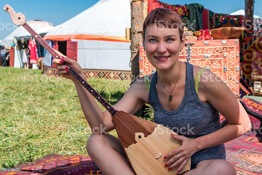girl playing in the Kazakh national musical instrument stock photo