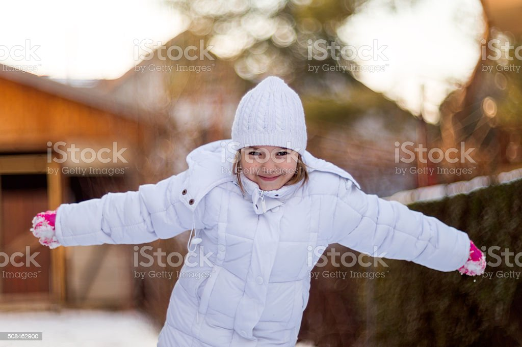 Girl (6-7) Playing in The Snow stock photo