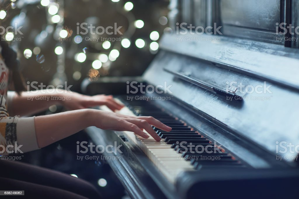 girl playing on an old piano. Beautiful blur background stock photo