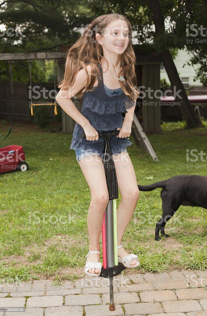 Girl playing on pogo stick in backyard stock photo
