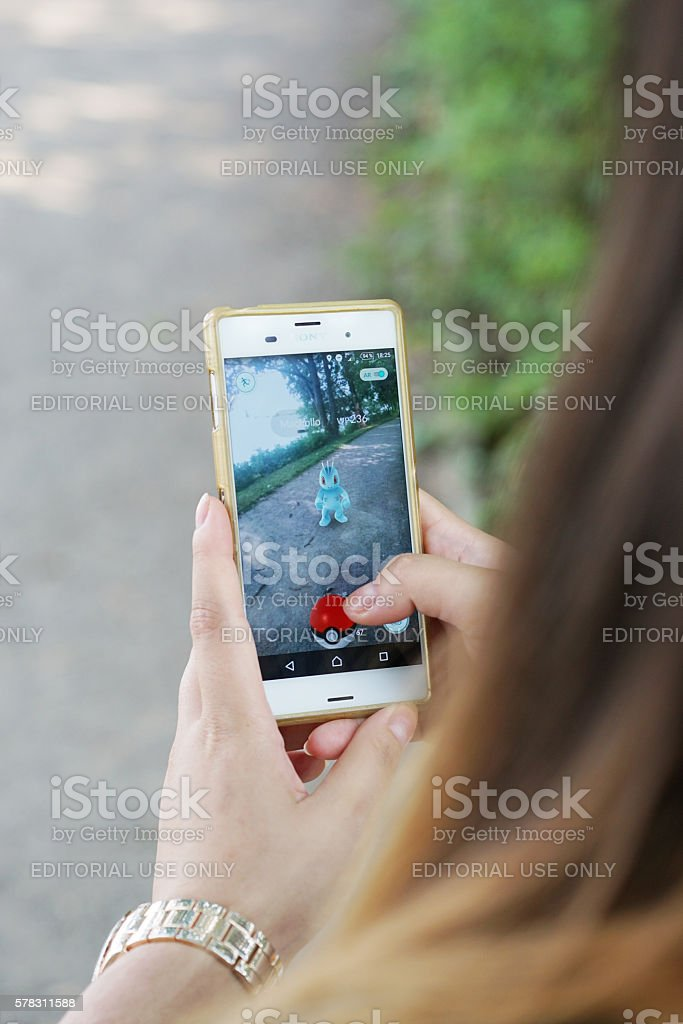 girl playing Pokemon Go on her smartphone stock photo