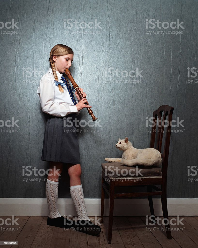 Girl playing recorder to cat royalty-free stock photo