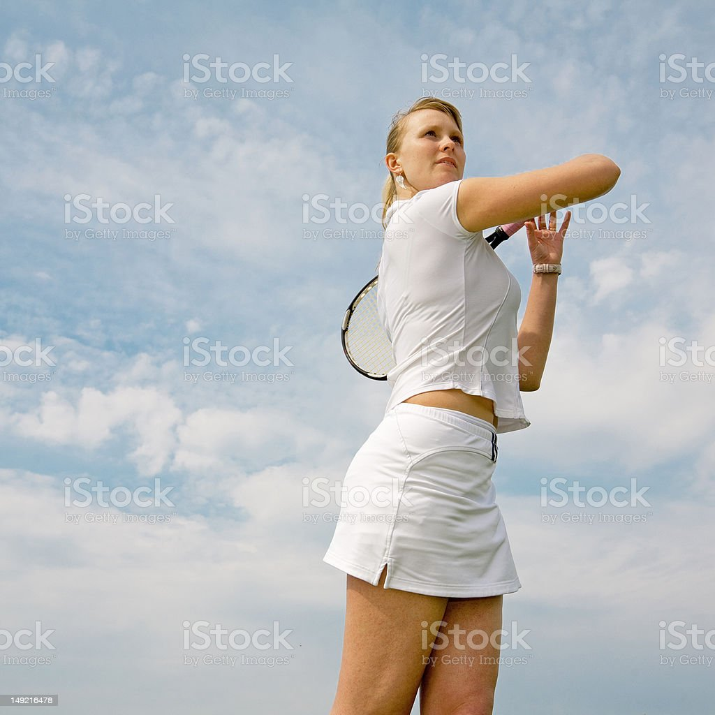 Girl playing tennis on background of sky royalty-free stock photo