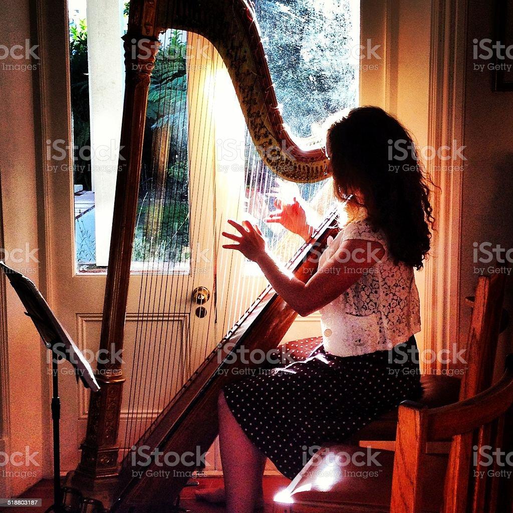 Girl playing the harp stock photo