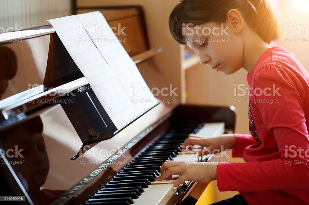 Girl playing the piano stock photo