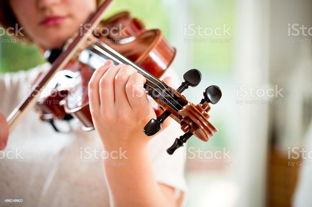 Girl playing violin at home stock photo
