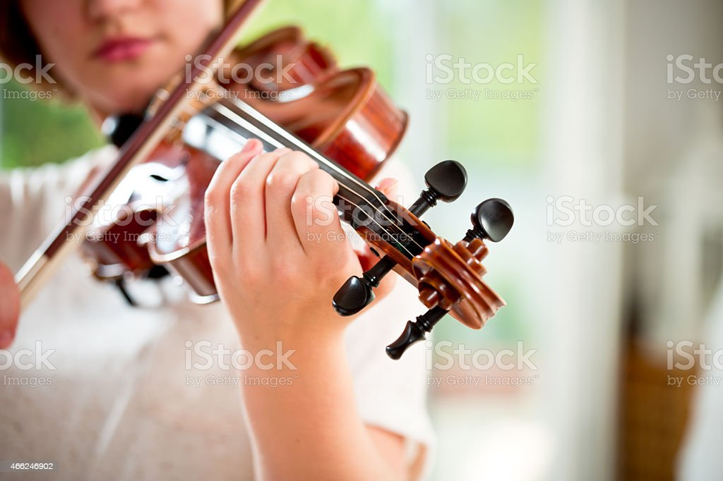 Girl playing violin at home stock photo