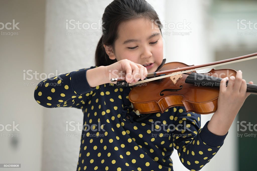 Girl Playing Violin Attentively stock photo