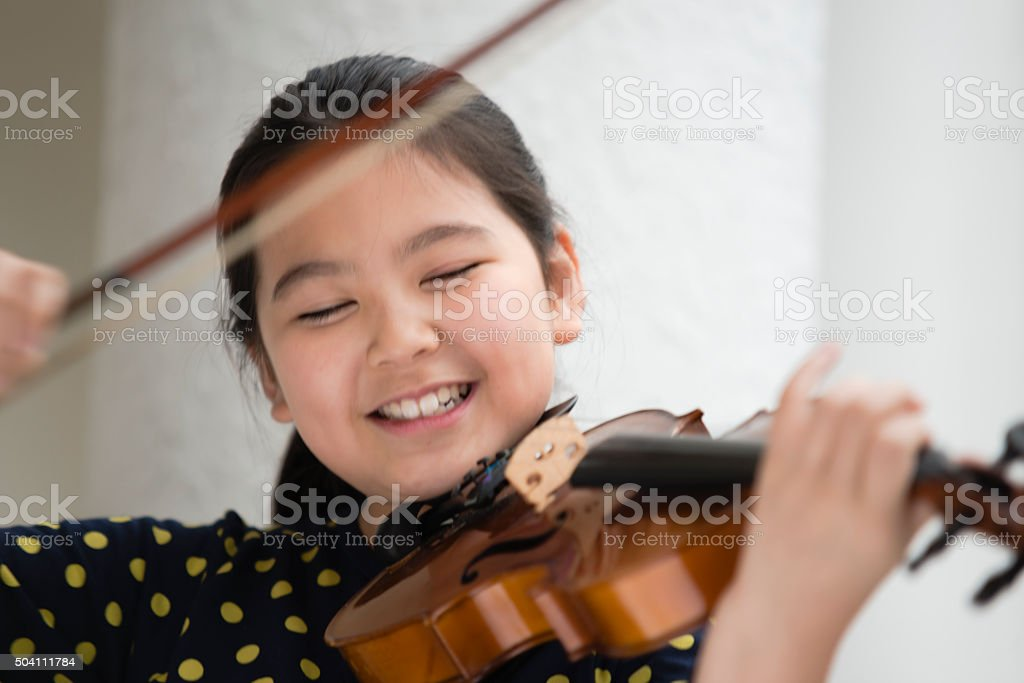 Girl Playing Violin with Great Joy stock photo