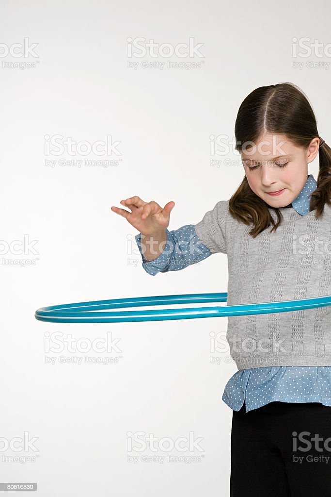 A girl playing with a plastic hoop royalty-free stock photo