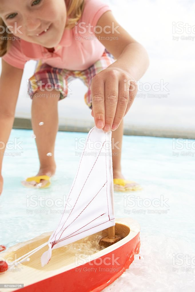 Girl playing with a toy sailboat stock photo
