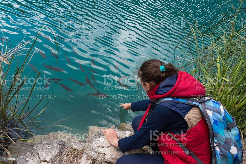 Girl playing with fish at Plitvice National Park stock photo