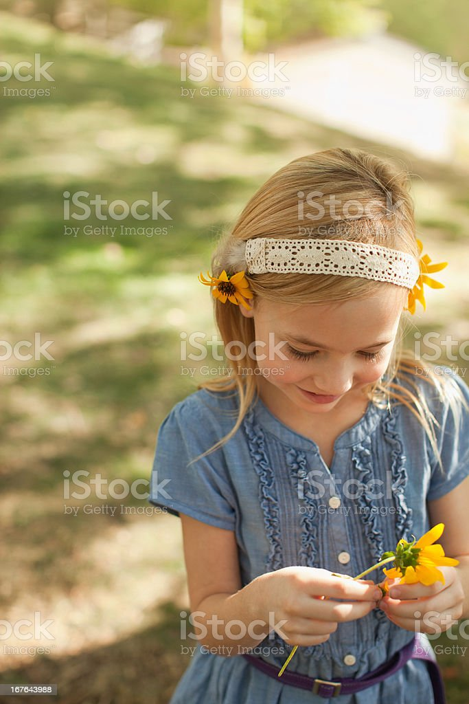 Girl playing with flowers outdoors stock photo