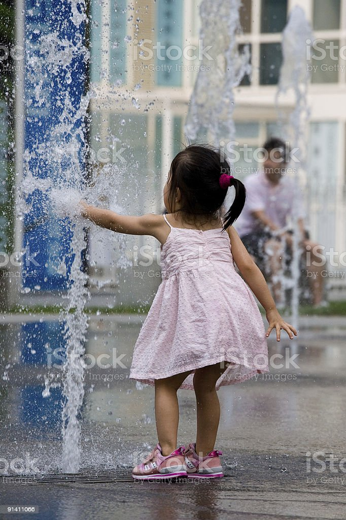 Girl playing with fountain stock photo